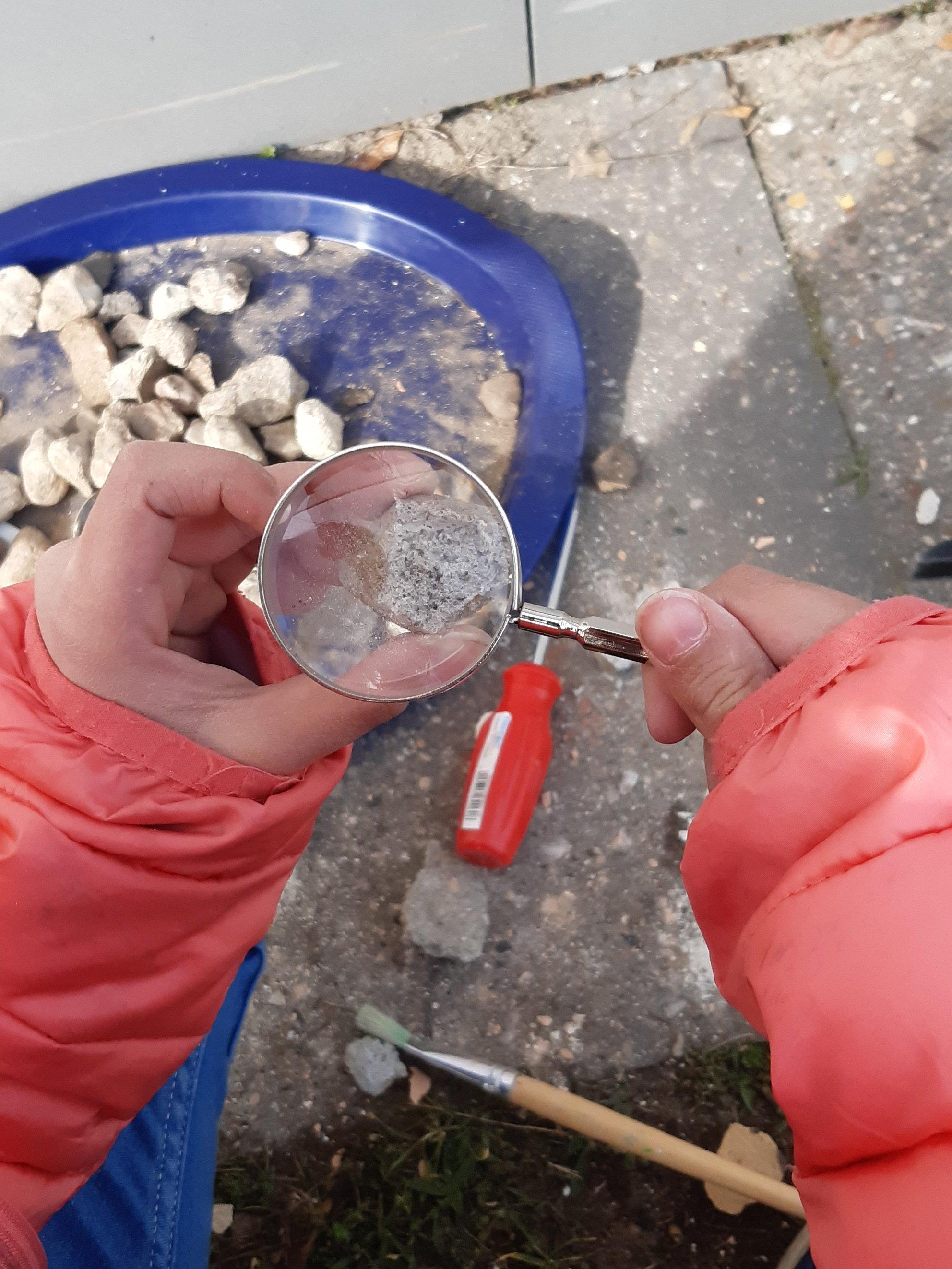 Kind untersucht Stein unter einer Handlupe.